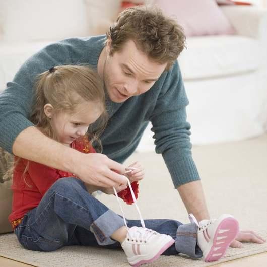 Папа учит дочку завязывать шнурки на белых кроссовках