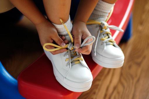 Ребенок самостоятельно завязывает себе бело-желтые шнурки